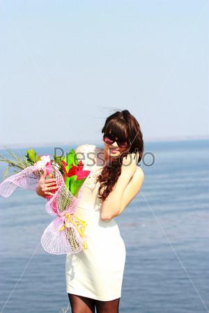 Девушка в солнцезащитных очках с букетом роз
