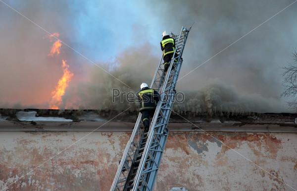 Фотография на тему Пожарные тушат огонь с высокой лестницы