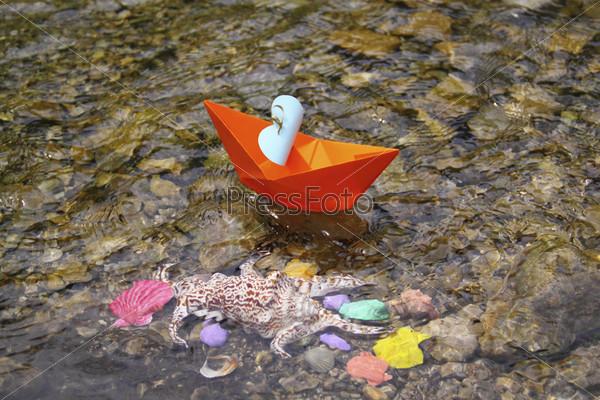 Оранжевый бумажный кораблик, плавающий в воде над красочными морскими ракушками