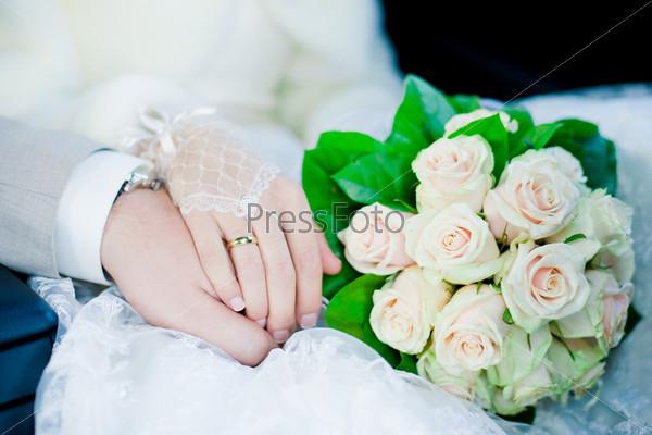 Руки и кольца на свадебном букете