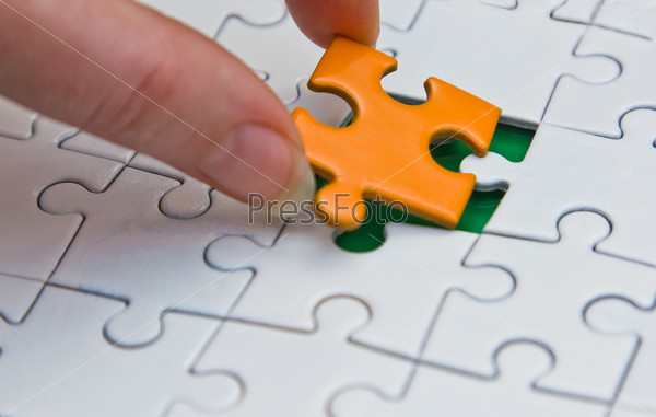 Руки размещают кусок головоломки