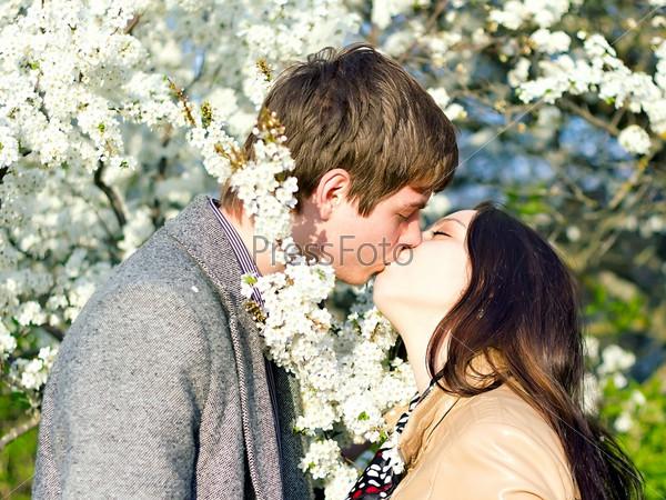Фотография на тему Весенний портрет молодой целующейся пары на природе