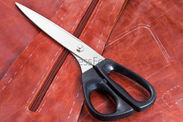 Портновские ножницы и узор на коричневой коже