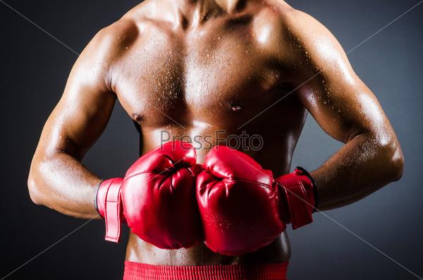 Боксер с красными перчатками в темной комнате