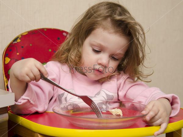 Фотография на тему Двухлетняя девочка ест вилкой за столом на кухне