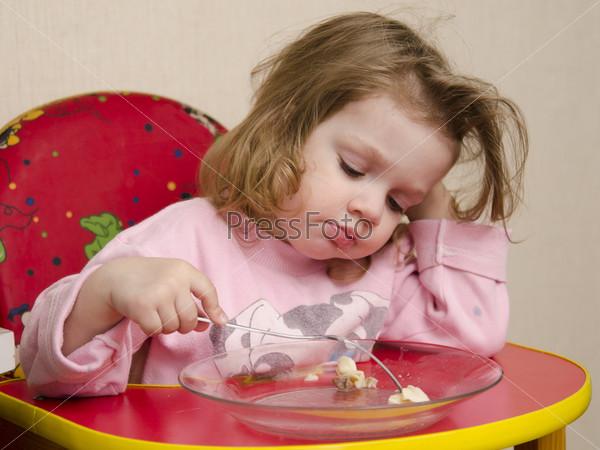 Двухлетняя девочка ест вилкой за столом на кухне