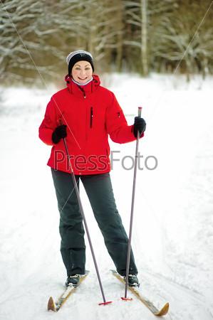 Счастливая девушка позирует на лыжах в зимнем лесу