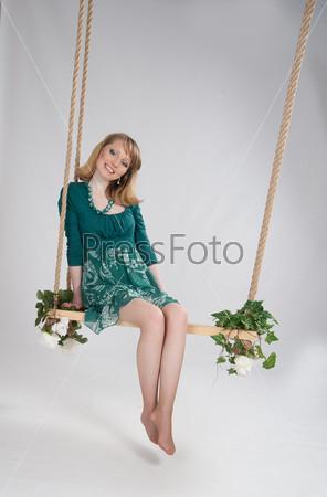 Красивая женщина в зеленом платье на качелях