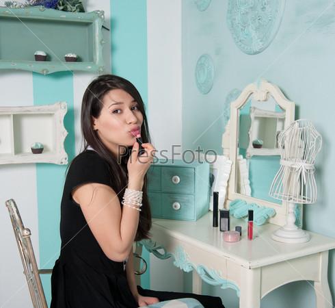 Красивая женщина красит губы