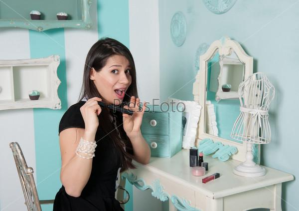 Женщина делает макияж перед зеркалом в комнате