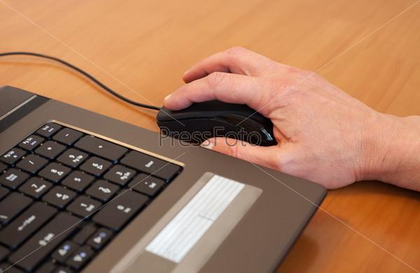 Человеческая рука на компьютерной мыши