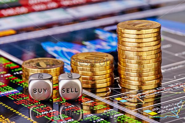 """Кости со словами """"продать"""" и """"купить"""", золотые монеты и финансовые диаграммы со столбцами котировок. Выборочный фокус"""