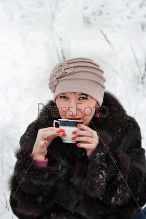 Женщина с чашкой чая в зимнем лесу