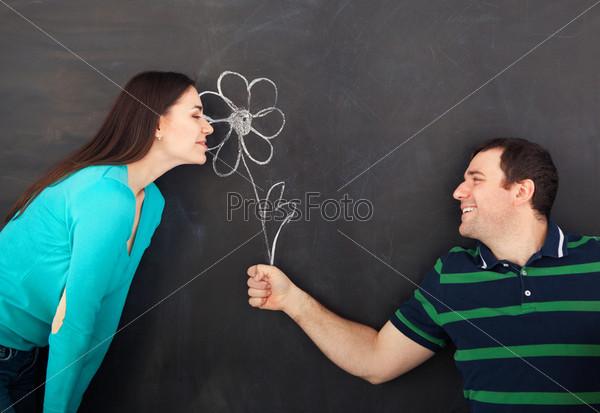 Фотография на тему Счастливая молодая пара с нарисованной мелом ромашкой