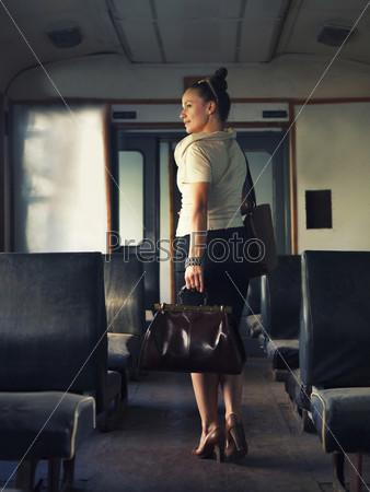 Женщина с чемоданом идет по вагону