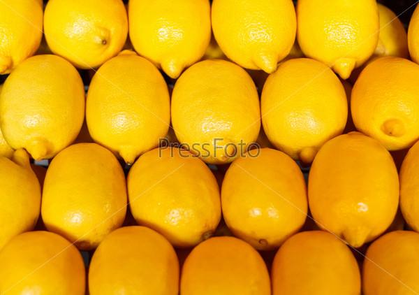 Желтый фон, много лимонов на рынке