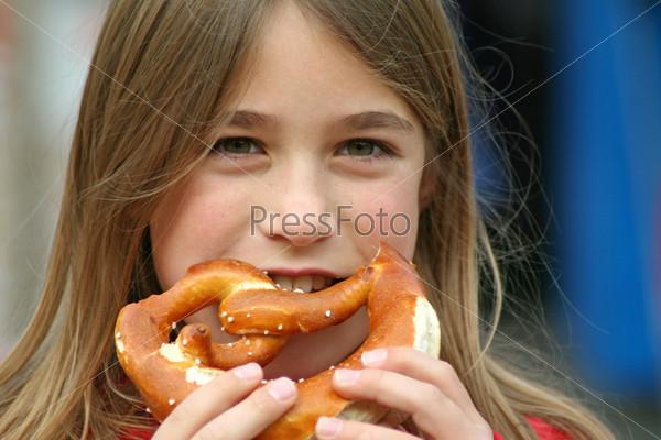 Молодая девочка ест хлеб