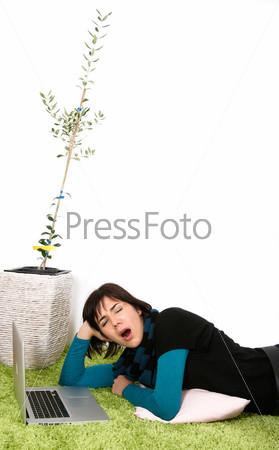 Женщина с ноутбуком зевает с оливковым деревом