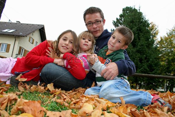 Фотография на тему Отец и трое детей в парке осенью