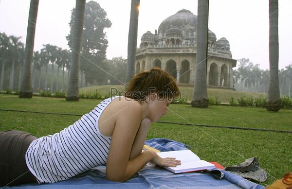 Женщина читает книгу в садах Лоди, Дели, Индия