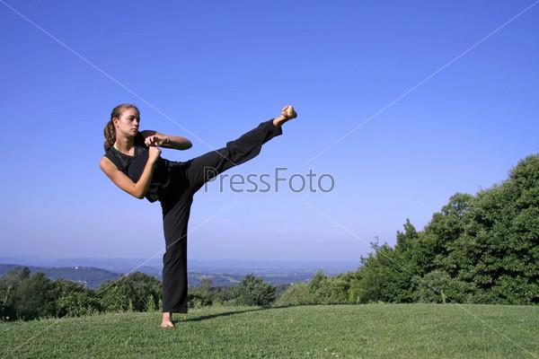Привлекательная молодая женщина обучается приемам самообороны