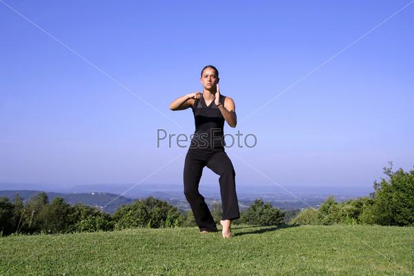 Фотография на тему Привлекательная молодая женщина обучается приемам самообороны
