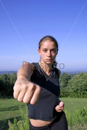 Кулак. Привлекательная молодая женщина обучается приемам самообороны