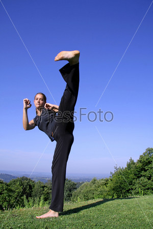 Удар ногой. Привлекательная молодая женщина обучается приемам самообороны