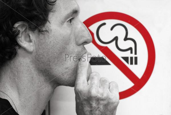 Человек курит и знак, запрещающий курение