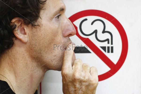 """Мужчина курит под знаком """"не курить"""""""