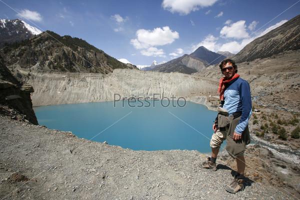 Мужчина стоит на краю скалы с видом на голубое горное озеро, Аннапурна, Непал
