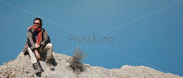 Путешественник сидит на горной вершине на фоне голубого озера