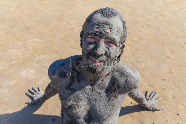 Человек, обмазанный целебной грязью