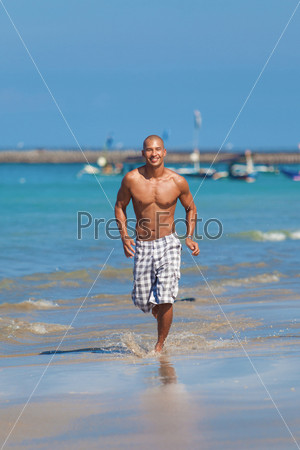 Молодой человек, бегущий по пляжу
