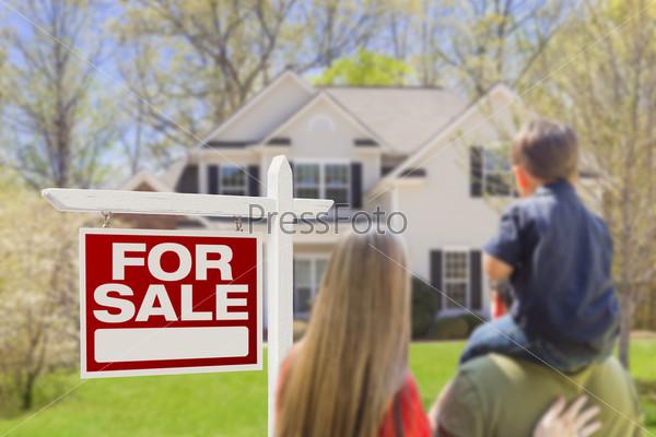 Семья стоит перед проданным домом и знаком о продаже