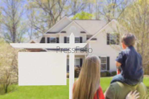 Фотография на тему Семья стоит перед домом и знаком о продаже