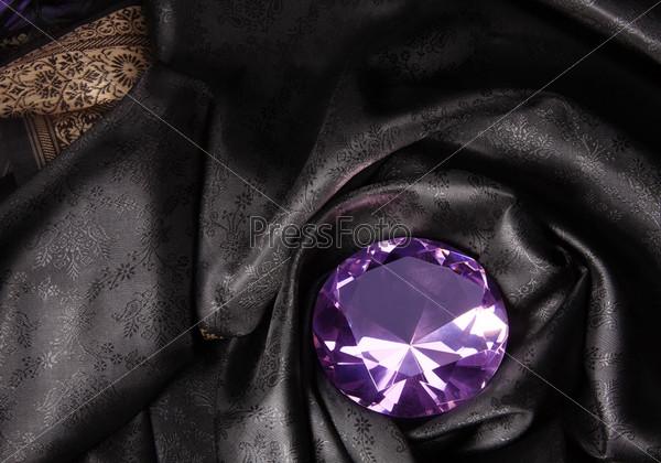 Розовый бриллиант в черной ткани