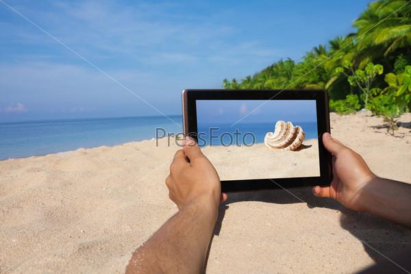 Руки с планшетным компьютером на пляже
