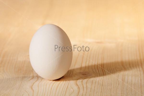 Белое яйцо на деревянном столе