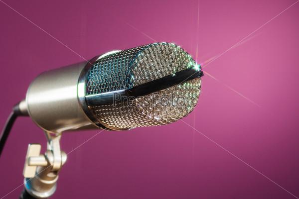 Металлический микрофон на розовом фоне
