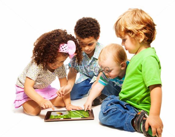 Фотография на тему Четыре ребенка играют с планшетом