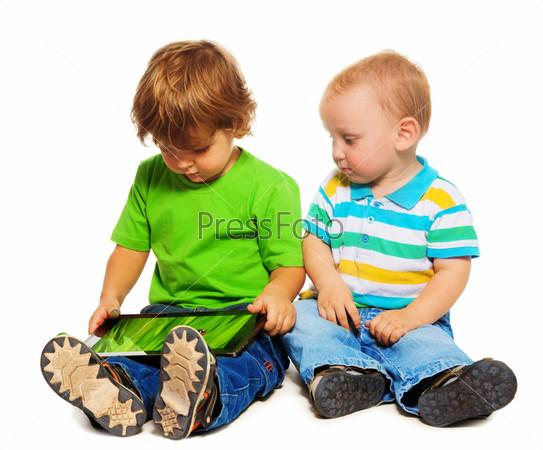 Двое детей игрют с планшетом