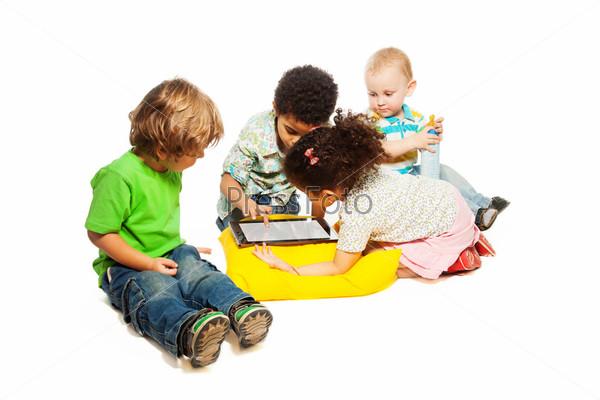 Четыре ребенка играют с планшетным компьютером