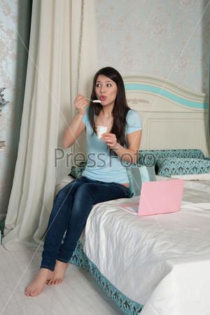 Фотография на тему Женщина с ноутбуком ест йогурт в постели