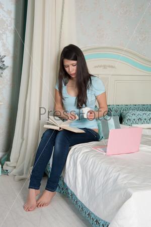 Женщина с ноутбуком ест йогурт в постели