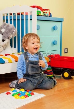 Смеющийся ребенок собирает мозаику