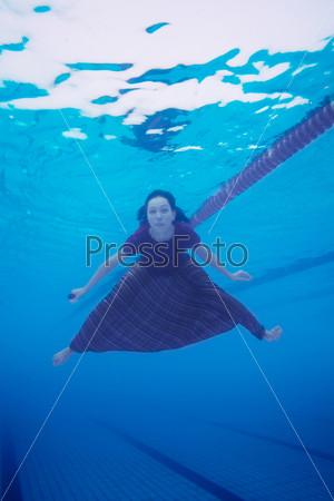 Женщина в одежде плывет в бассейне