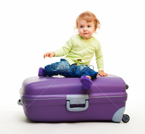 Малыш сидит на большом чемодане