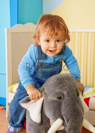 Малыш верхом на игрушечном слоне