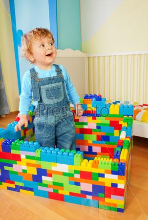 Малыш строит замок из пластиковых блоков